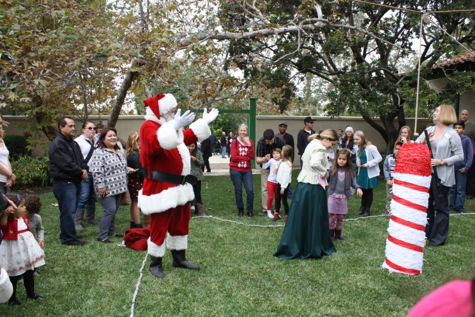 Rancho Los Cerritos hosts its Old Time Christmas Festival on Sunday, December 8, 2019. (Image - Santa in RLC courtyard w families and kids with a pinata.)
