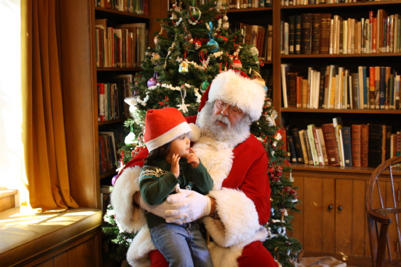 The 2019 Cocoa with Santa events will be held three days December 5, 6, and 7. Tickets on sale November 1, 2019. (Photo - Santa w a child on lap in front of Christmas Tree)