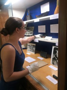 Rancho Los Cerritos' volunteer curatorial intern Nevada Evers installs the latest special exhibit in the library case in commemoration of the 175th anniversary of the adobe's construction (built in 1844) and specifically the sheep ranching years (1866-1929).