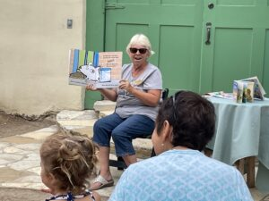 Rancho Los Cerritos Storytime Reader presenting book to a mother and child