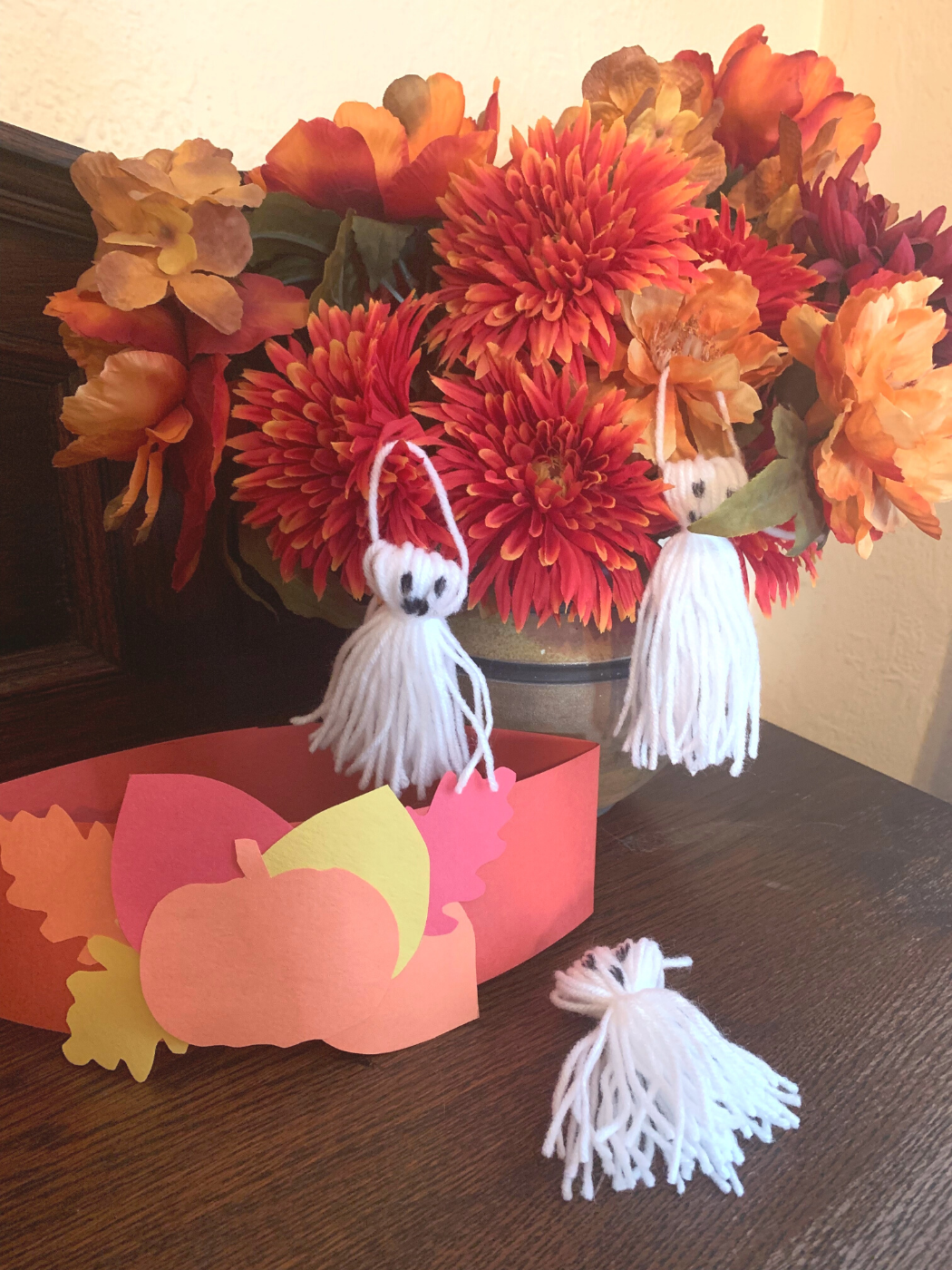 A pumpkin headband and three ghost crafts on a table in front of a fall flower arrangement